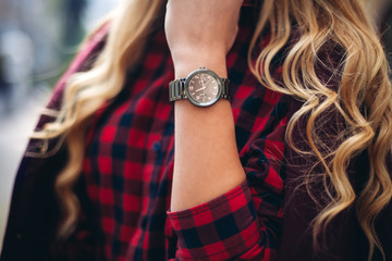 Elegant, trendy outfit Closeup of wrist watch on the hand of stylish woman. Fashionable girl on the street. Female fashion.