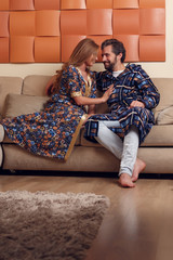 Image of long-haired blonde and men in homemade clothes hugging on sofa