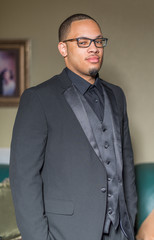 Young Black man standing in a suit with glasses on