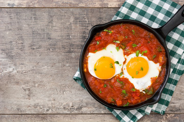 Mexican breakfast: Huevos rancheros in iron frying pan on wooden table top view copyspace