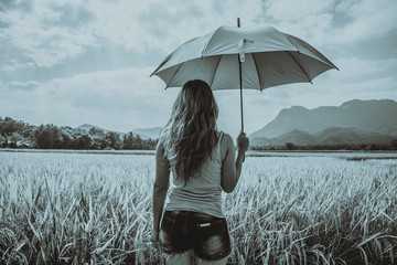 Asian women relax in the holiday.Standing Umbrella On the rice field in the countryside on holiday. black and white picture