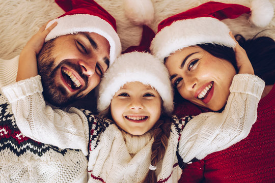 Christmas family! Happy mom,dad and little daughter on Santa Claus hats lying down. Enjoyng love hugs, holidays people concept