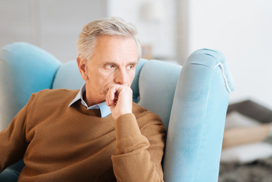 If I had my time over again. Thoughtful old gentleman sitting in a chair and musing over his memories while spending his day at home.