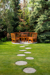 Sunny day in a spring garden with wooden table and benches