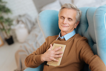 She is my everything. Joyful old man relaxing in a chair with a photo on his chest and smiling while dreaming of his wife.