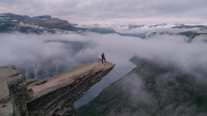Siedzi na skraju Trolltunga w Norwegii wczesnym rankiem.
