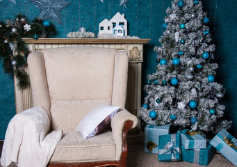Christmas tree with blue and white toys and gift boxes in the interior