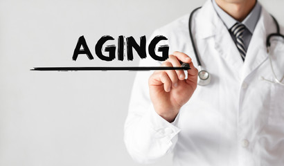 Doctor writing word Aging with marker, Medical concept