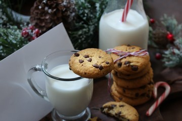 Chocolate chip cookies milk and letter for Santa on festive Xmas background