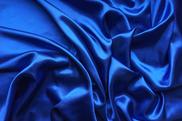 Blue satin, silky fabric, wave, draperies. Beautiful textile backdrop. Close-up. Top view