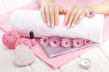 Poster de jardin Manicure beautiful pink manicure with chrysanthemum flower and towel on the white wooden table. spa