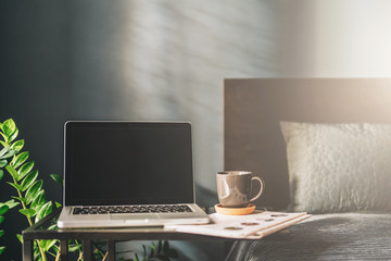 Workplace in bad room without people, close-up of laptop with blank screen on table. Space for text, logo, advertising.Nearby is newspaper, cup of coffee. On background bad, pillow. Mock up. Nobody.