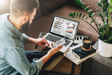 Young man, entrepreneur, freelancer sits at home on couch at coffee table, uses smartphone, working on laptop with graphs, charts, diagrams on screen.Online marketing,education, e-learning. Startup.