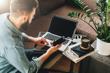 Young bearded hipster man, entrepreneur, freelancer dressed in denim shirt, sits at home on couch at coffee table, uses smartphone, working on laptop. Online marketing, education, e-learning. Startup.