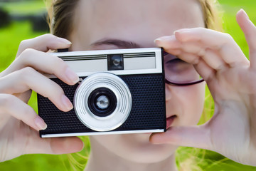 girl with retro camera, outdoor. bright sunny, green background