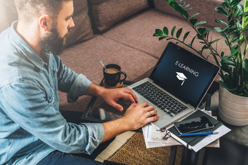Young bearded hipster man,entrepreneur sits on couch at coffee table,uses laptop with inscription- e-learning on screen.On table notebook,cup of coffee.Online marketing,education,e-learning.Startup.