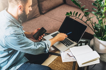 Rear view. Young bearded hipster man, entrepreneur, dressed in denim shirt, sits at home on couch at coffee table, holding smartphone, showing pencil on screen of laptop. Online marketing, e-learning.