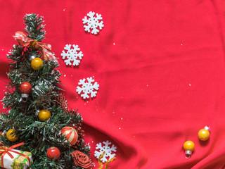 Christmas tree, white snowflakes, Christmas balls on a red background. Christmas background. Free space for text. Top view