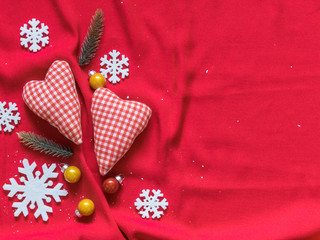 Two soft hearts, white snowflakes, Christmas balls on a red background. Christmas background. Valentine's day background. Free space for text. Top view