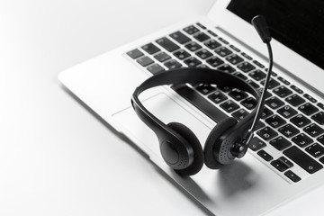 call center support concept. headset on keyboard computer laptop