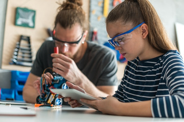 Father and daughter fixing robotic toy car