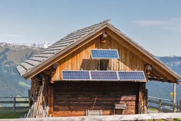 Wooden shepherd lodge with Alpine mountain landscape in Austria.