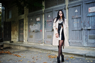 Black hair woman in glasses and coat posed on idustrial street.