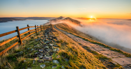 Thick cloud inversion with morning sun casting golden light on the landscape. Taken at Mam Tor in the English Peak District.