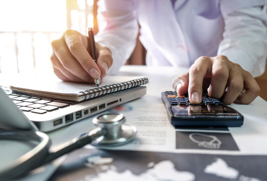 Healthcare costs and fees concept.Hand of smart doctor used a calculator and smartphone for medical costs at modern hospital in sun light