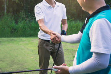 Golfers are shaking hands and smiling when meeting on a golf course. Golfers congratulating after the game