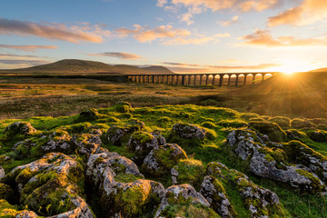 Foto op Aluminium Noord Europa Gorgeous golden light as the sun sets behind the Ribblehead Viaduct with rocks in foreground.