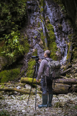 Professional photographer with cameras on tripod shooting in a river
