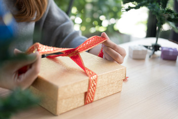 woman tying xmas gift box with ribbon.  Process of package xmas present.  greetings for winter holidays. christmas, new year celebration.