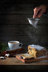 christmas cake, in germany christstollen is sprinkled with icing sugar, coffee cup, spices and cinnamon star cookies on a rustic wooden table, dark vintage background with copy space, vertical