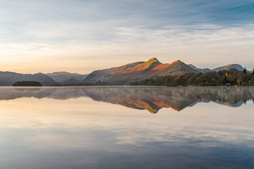 Morning golden light hitting mountains with calm reflections in lake. Taken at Derwentwater in the English Lake District.