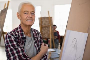 Portrait senior man standing by easel