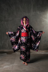 young girl with pink, curly hair in a colored kimono on a black background