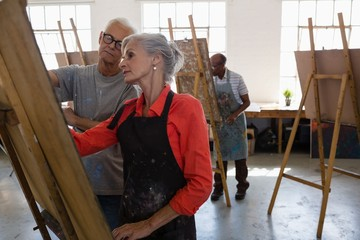 Senior man looking at woman painting on easel