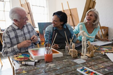 Cheerful senior male and female artists at table