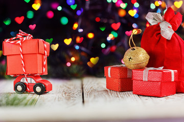 Miniature Red Car Carrying a big red box on colorful bokeh background. Holiday Merry Christmas concept.