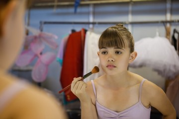Cropped image of girl applying blush while reflecting in mirror
