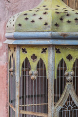 Isolated, close-up of a patina metal, antique birdcage with a stone wall background