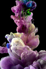 Macro close-ups of colorful liquids that appeared for a brief second when the flow of color drops spread underwater. A colorful mix of fluids is Isolated on black background.