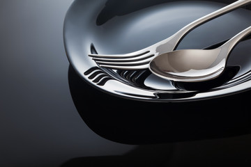 Empty plate with spoon and fork on a black background