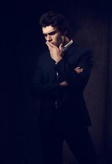 Thinking depression charismatic man looking down on dark shadow dramatic light background. Closeup portrait
