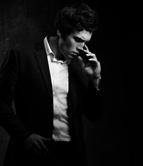 Thinking charismatic man posing and looking down on dark shadow dramatic light background. Closeup portrait. Black and white