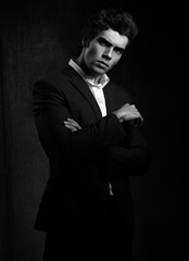 Handsome male model posing in fashion suit and white style shirt looking on dark shadow background. Black and white portrait