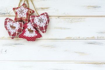 Christmas Card with Hanging Fabric Heart,Pine Tree and Star on a White Wooden Background