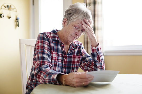 Elderly woman worry about bill notice at home