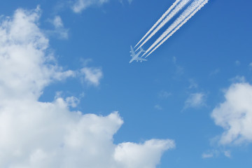 White airliner transports passengers while it pulling white contrails in blue cloudy sky